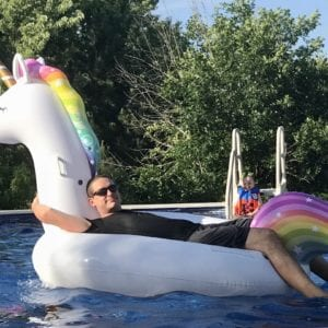 Steven floating on unicorn float in pool